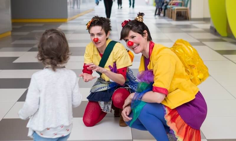 2 Clowndoctors with young patient in hospital setting